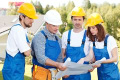 Builders in hardhats with blueprint. Team of Builders in hardhats with blueprint outdoors Royalty Free Stock Photography