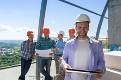 Team Of Builders On Site lyckligt le för leverantörhållplan över lärlinggruppen som diskuterar ritningen royaltyfri bild