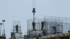 Workers at building under construction. Team of builders works on the high floors of the building under construction stock footage