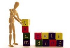 Team Building. A wooden man stacks up blocks to build the words team building Royalty Free Stock Photos