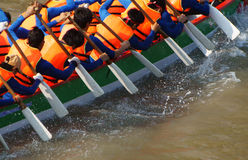 Team building activity,  rowing dragon boat race. Team building activity on water, group of strong, active man rowing dragon boat race, they try to row with high Royalty Free Stock Images