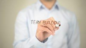 Team Building, Mann-Schreiben auf transparentem Schirm Stockbild