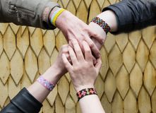 Team building in nature. Many hands in bright bracelets together royalty free stock image