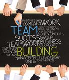 Team building. Photo of business hands holding blackboard and writing TEAM BUILDING Royalty Free Stock Image