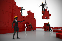 Team building a red jigsaw puzzle Royalty Free Stock Photo