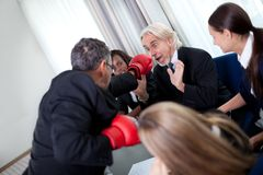 Team of business associates fighting in the office Royalty Free Stock Images