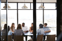Team in a business boardroom meeting seen through glass wall Royalty Free Stock Image