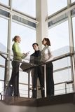Team in the business building. Two girls and man are talking in the building with glassy walls Royalty Free Stock Images
