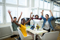 Team of business executives with arms up at desk royalty free stock images