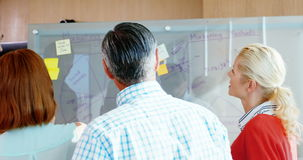 Team of business executives discussing over glass board. In office