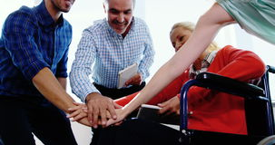 Team of business executives forming handstack. In office
