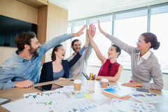 Team of business executives giving high five in conference room. At office royalty free stock photos