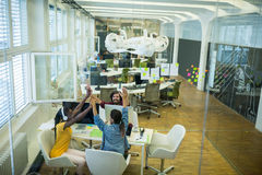 Team of business executives giving high five at desk stock photo