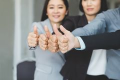 Team of business join forces working and showing thumbs up as si stock image