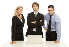 Team of business people. Three business people confidently stand near a table with a laptop Stock Image