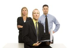 Team of business people. Three business people confidently stand near a table with a laptop Stock Photo