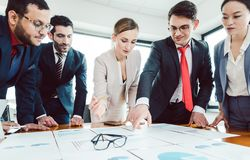 Team of business people analyzing numbers and charts stock image