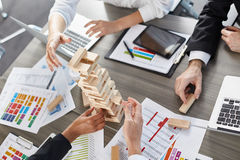 Team of business people build a wooden construction. concept of teamwork and partnership royalty free stock photos