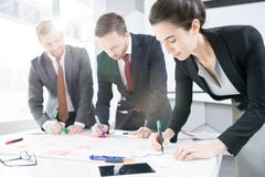 Team of Business People Collaborating on Project. Portrait of successful business people actively collaborating on strategy project in sunlight royalty free stock images