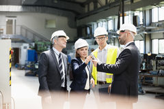 Team of business people examining machine part in metal industry stock image