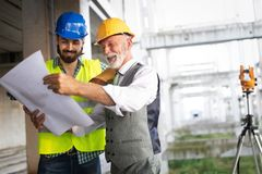 Team of business people in group, architect and engeneer on building site check documents royalty free stock photo