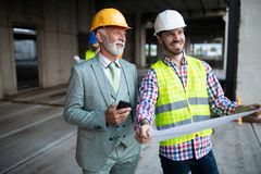 Team of business people in group, architect and engeneer on building site check documents stock image