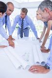 Team of business people looking at construction plan Royalty Free Stock Photo