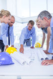 Team of business people looking at construction plan Stock Images