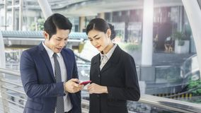 Team of business people smart man and woman use smart phone. Team of business people smart men and women talk and use smart phone in good feeling at outdoor Royalty Free Stock Images