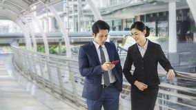 Team of business people smart man and woman use smart phone. Team of business people smart men and women talk and use smart phone in good feeling at outdoor Royalty Free Stock Photos
