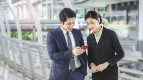 Team of business people smart man and woman use smart phone. Team of business people smart men and women talk and use smart phone in good feeling at outdoor Royalty Free Stock Photography