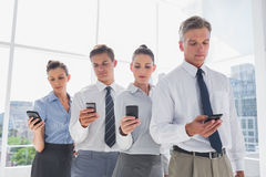 Team of business people standing together in line with their mob Stock Image