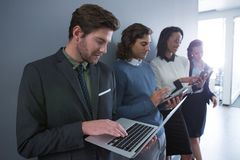 Team of business people using electronic devices Stock Image