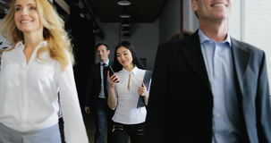 Team of business people walking in office while asian businesswoman answer phone call