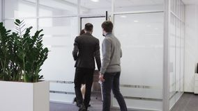 Team of business people walks into meeting room at office stock footage