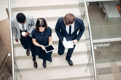 Three multiracial business people walking down on stairs with digital tablet. Team business people wear suit and walking down on step of stair and holding Royalty Free Stock Images