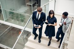 Three multiracial business people walking down on stairs with digital tablet. Team business people wear suit and walking down on step of stair and holding Royalty Free Stock Image