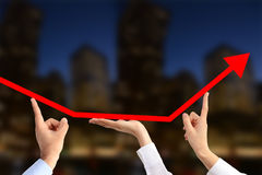 Team of business people working together for economic growth. Supporting  with their hands an arrow graph chart going upwards on a blurred urban background Stock Photography