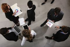 Team of business person works together on company statistics. Shooted from above. Concept of teamwork and partnership royalty free stock photos