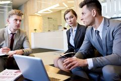 Team of Business Professionals Collaborating in Office. Group of three young business people using laptop and collaborating on project sitting at coffee table in royalty free stock photography