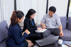 Team of business three people working together on a laptop with Royalty Free Stock Photos