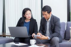 Team of business two people working together on a laptop with during a meeting. Sitting around a table Stock Images