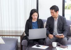 Team of business two people working together on a laptop. With during a meeting sitting around a table Royalty Free Stock Image