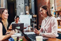 Team of business women working with papers using laptops sitting at desk in office royalty free stock photos