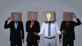 Team of businessman hiding head with box and gesturing stock video