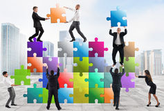 Team of businesspeople build a new company. Team of businesspeople build a puzzle construction stock image