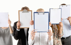 Team of businesspeople holding a folders near face Royalty Free Stock Image