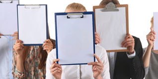 Team of businesspeople holding a folders near face isolated on white background Stock Photography