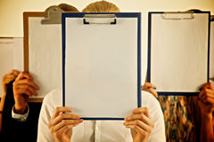 Team of businesspeople holding a folders near face Royalty Free Stock Photography