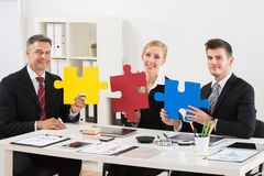 Team Of Businesspeople Holding Jigsaw Puzzle. Team Of Happy Businesspeople Holding Multi-colored Jigsaw Puzzle In Office stock photography